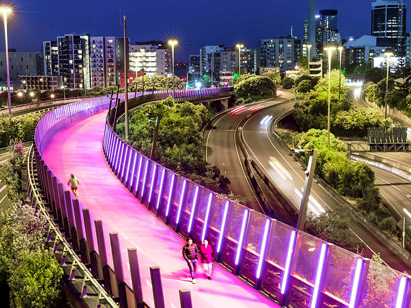 https://rfacdn.nz/corporate/assets/media/about-us-gallery-people-walking-and-jogging-across-te-ara-i-whiti-the-pink-lightpath-at-night-in-auckland.jpg